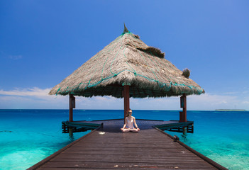 Girl in sunglasses meditating on the terrace in the Maldives