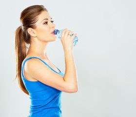 portrait of active woman drinking mineral water of bottle