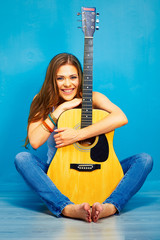 Musician girl with acoustic guitar sitting on a floor