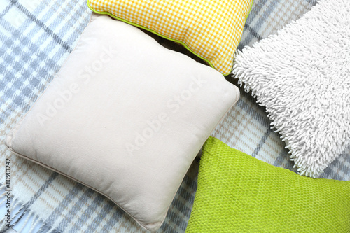 Poster Decorative pillows on plaid close up