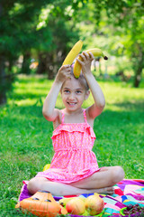 Little beautiful girl child kid sitting on grass with bananas