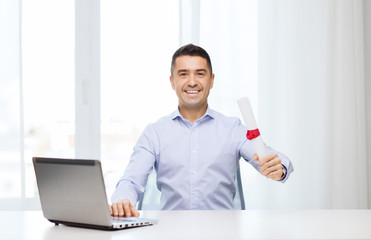smiling man with diploma and laptop at office