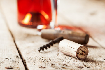 Wine cork and corkscrew on wooden table, wine bottle and glass