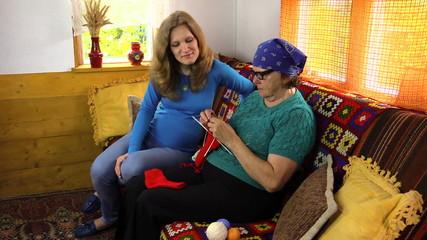 Grandma teaching pregnant granddaughter how to knit