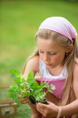Mädchen im Garten pflanzt Kräuter an