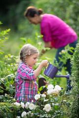 Mädchen und Oma bei der Gartenarbeit, Blumen gießen