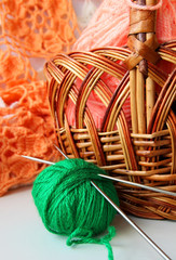 Ball of yarn and knitting needles lying near basket.