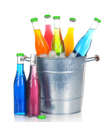 Bottles of tasty drink in metal bucket with ice isolated