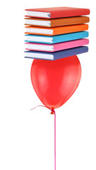 Stack of books balancing on red balloon