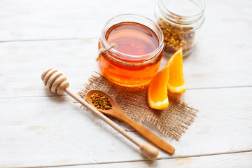 Honey in a glass jar and orange on a white background wooden