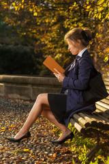 Ragazza sulla panchina in un parco che legge un libro