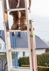 Handwerker auf einer Leiter am Haus