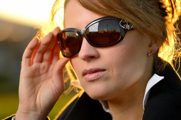 Ragazza che si sistema gli occhiali da sole