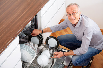 Senior man in kitchen, empty out the dishwasher 5
