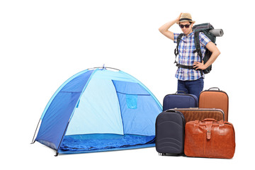 Baffled tourist standing by a tent and five briefcases