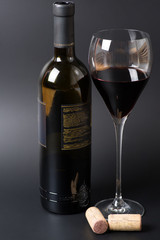 Red wine bottle and glass with cork on a black background