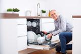 Senior man in kitchen, empty out the dishwasher 8