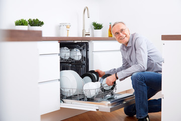 Senior man in kitchen, empty out the dishwasher 8