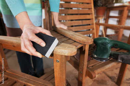 Leinwanddruck Bild Sanding and painting an outdoor bench