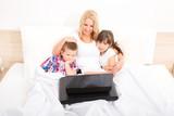 Mutter und Kinder mit Laptop im Bett