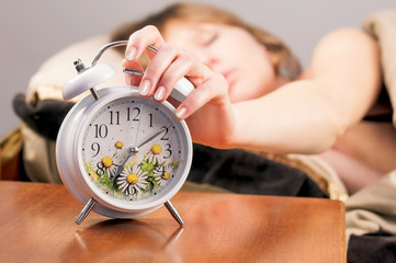 alarm clock and sleeping girl on the background