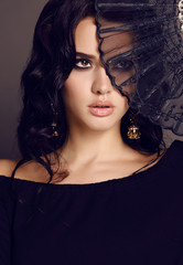 sensual woman with dark hair holding black lace fan in hand