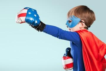 Child. Superhero kid against dramatic blue sky background