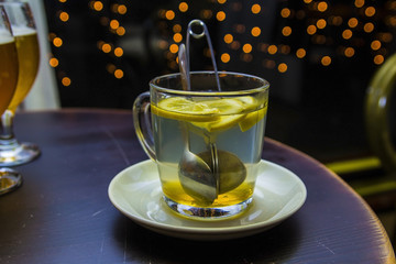 cup brewing tea in a cafe on the background of lights