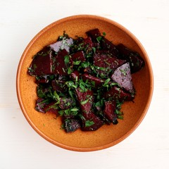 Stewed beetroot with chard in clay bowl