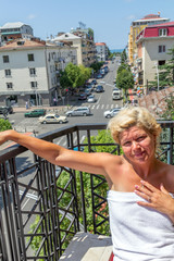 Cheerful tanned blonde looks from the balcony