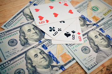 Four aces poker playing cards among U.S. dollar banknotes