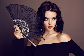 beautiful woman with dark hair holding black lace fan in hand