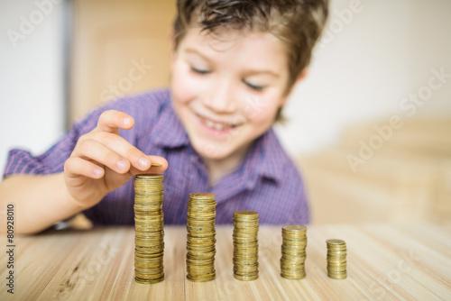 Leinwanddruck Bild Boy puts the coin