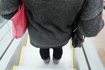 Rear view of woman using the escalator