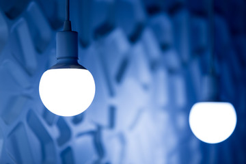 two light bulbs on  background of blue volume wall