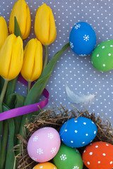 Easter eggs in the nest with yellow tulips