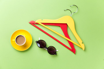 Cup of coffee and hangers with sunglasses