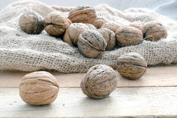 Some nuts on a sack on a wooden table