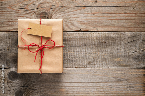 Leinwanddruck Bild Gift box with tag on wooden background
