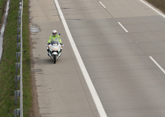 Policeman drives motorbike on highway in sunny day