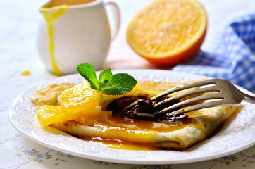 Crepes with chocolate filling and orange syrup.