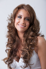 Beautiful smiling woman with healthy long curly hair