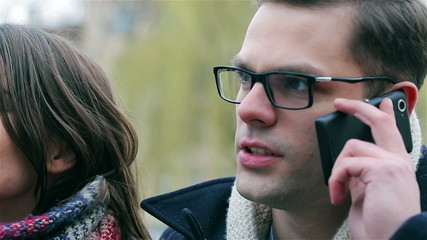 Man talking on cellphone and his girlfriend looking at him