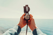 Leinwanddruck Bild - Traveler holding a compass on background of sea