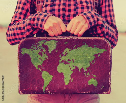 Woman holding small suitcase with a map - 80939439