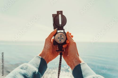 Leinwanddruck Bild Traveler holding a compass on background of sea
