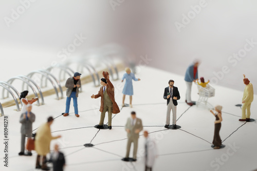 Fototapeta close up of miniature people with social network diagram on open