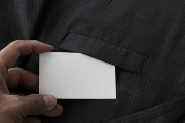 close up of hand picking blank business card from gray suit pock