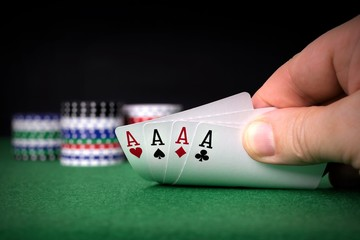 A poker hand of four aces with chips and copy space background
