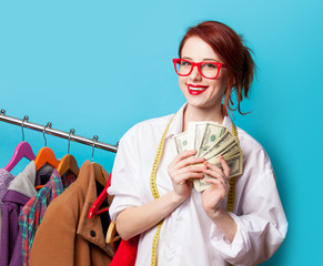 Young redhead designer with dollars